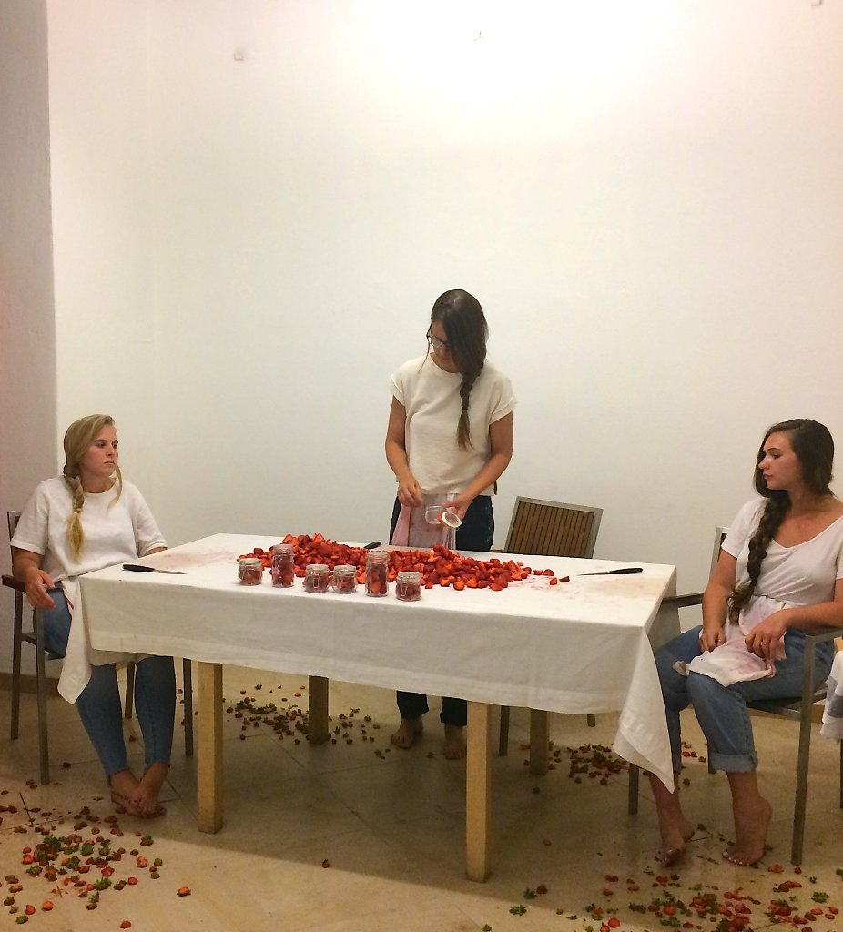 A trinity of female performers pares strawberries at a table.